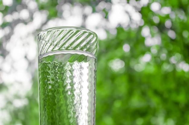 Acqua in un bicchiere di vetro trasparente sullo sfondo della finestra