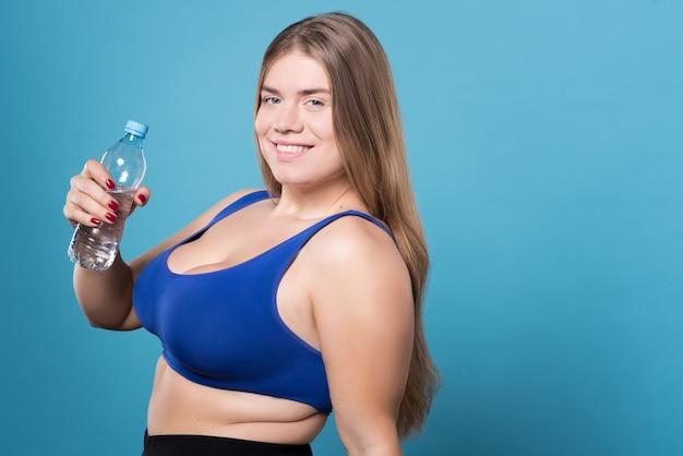 L'acqua è vita. primo piano di bella giovane donna paffuta sorridente in piedi con una bottiglia d'acqua.