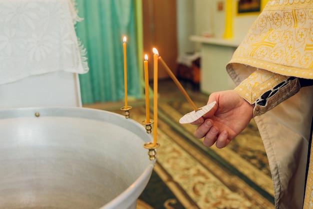 L'acqua viene versata nella fonte per fare il bagno al bambino nella chiesa, tradizioni religiose.