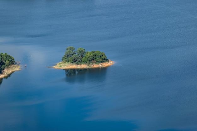 L'acqua del lago è blu, gli alberi in riva al lago sono verdi e c'è un'isola nel lago