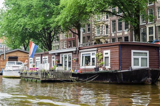 Vista del livello dell'acqua da uno dei canali di una classica casa galleggiante ad amsterdam, paesi bassi