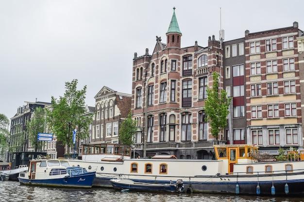 Vista del livello dell'acqua da uno dei canali degli edifici storici e delle barche ad amsterdam, paesi bassi