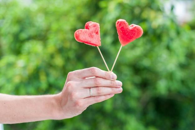Anguria tagliata a forma di cuore in mano. concetto di amore. san valentino