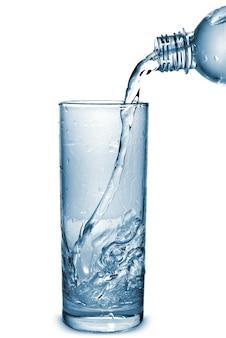 Acqua che versa in vetro dalla bottiglia isolata su bianco