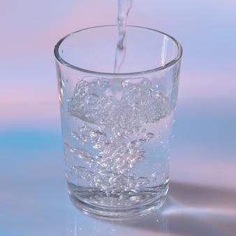 Acqua che versa nel bicchiere su sfondo bianco con luci al neon