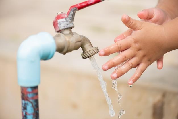Acqua che si versa nelle mani della bambina. concetto di water day.
