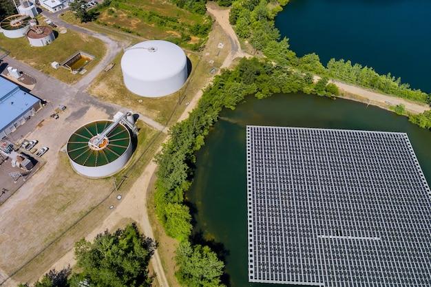 La purificazione dell'acqua è il processo di rimozione di sostanze chimiche indesiderabili moderno impianto di trattamento delle acque reflue urbane vicino alla piattaforma di celle di pannelli solari galleggianti sul bellissimo lago