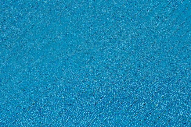 Acqua increspature sulla piscina piastrellata blu sullo sfondo