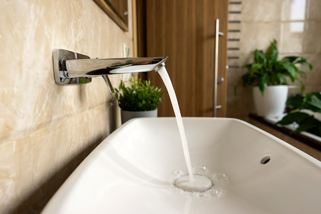 Acqua che scorre dalla gru nel lavandino del bagno moderno