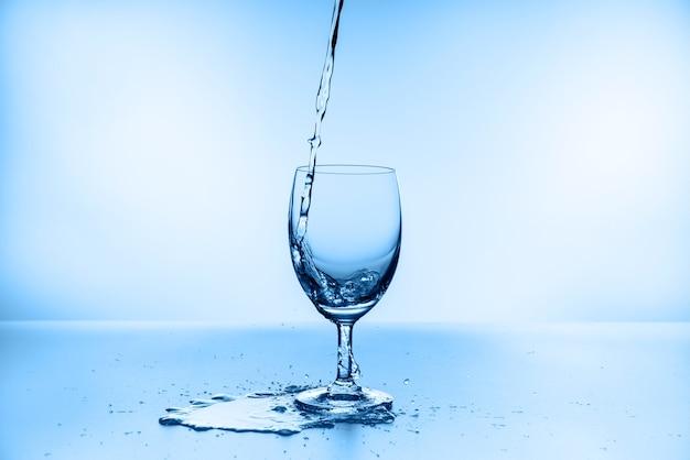 Accumulazione della spruzzata dell'acqua nel bicchiere di vino isolato sull'azzurro
