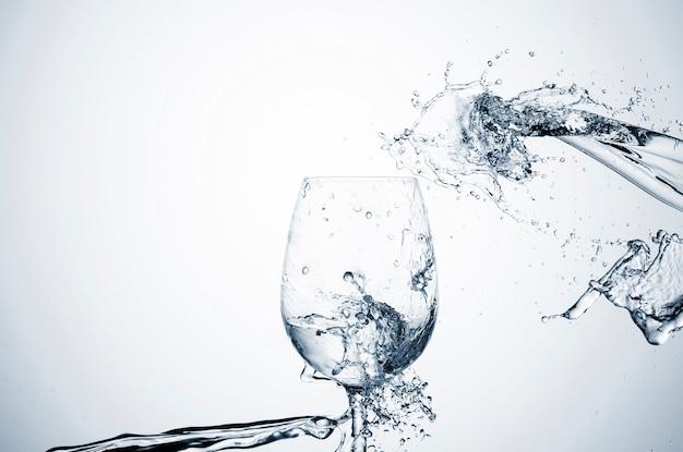 Spruzzata dell'acqua in vetro trasparente con lo spazio della copia