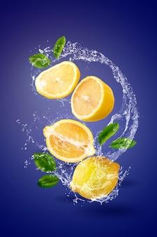 Acqua che spruzza sulla frutta gialla del limone sopra la parete blu.
