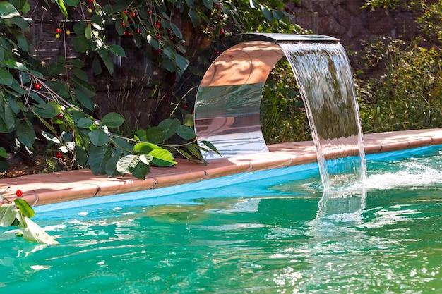 Rifornimento d'acqua alla piscina da una cascata. sistema di ricircolo e pulizia.