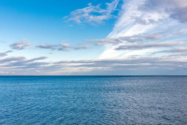 Superficie dell'acqua del mare e nuvole nel cielo blu