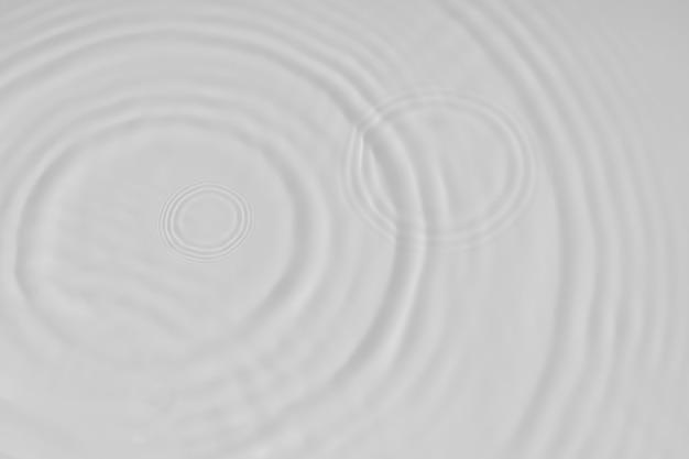 Cerchi e bolle di struttura dell'acqua del fondo dell'ondulazione dell'acqua tranquilla su una superficie bianca liquida