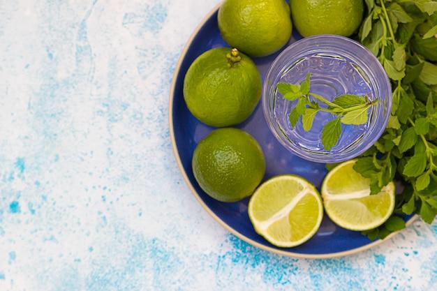 Acqua, lime intero e mezzo, menta su piatto di ceramica blu. ingredienti per fare rinfresco bevanda estiva.