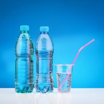 Acqua con gas in vetro plastica con cannuccia rosa. bottiglia con acqua fresca sul tavolo bianco e sfondo blu.
