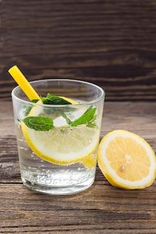 Acqua con limone e menta in un bicchiere su un tavolo di legno. limonata fresca estiva con cannuccia