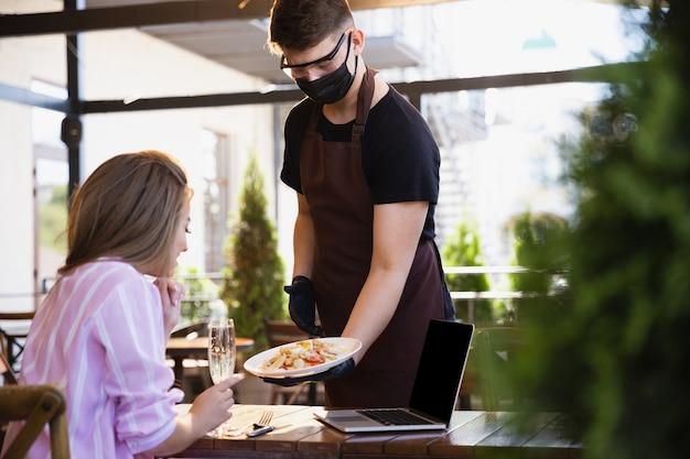 Acqua che lavora con maschera facciale nel ristorante, focolaio di coronavirus