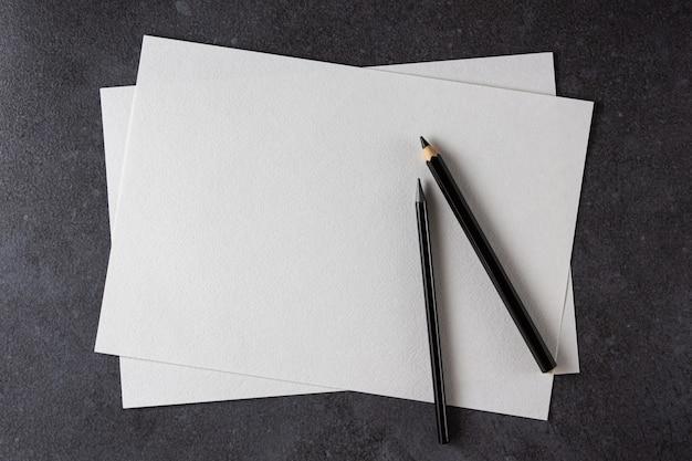 Carta a4 dell'acquerello con matite nere su fondo nero. vista dall'alto.