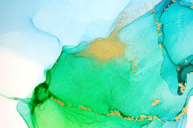 L'estratto dell'acquerello verde blu e oro macchia la trama sfumata dell'inchiostro del fondo