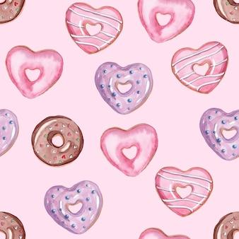 Modello senza cuciture di ciambelle a forma di cuore dell'acquerello su sfondo rosa