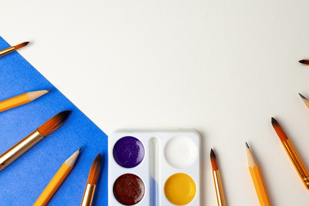 Scatola di pittura ad acquerello e set di pennelli su blu e bianco, piatto laici