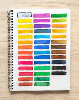 Pittura ad acquerello su carta bianca per notebook con fondo in legno. collezione di tonalità colorate su carta bianca. set di pennello acquerello multicolore. avvicinamento.