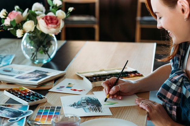 Pittura ad acquerello. artista al lavoro. pittore femminile sorridente che fa le pennellate della miscela di colore. schizzi e forniture di tavolozze in giro.