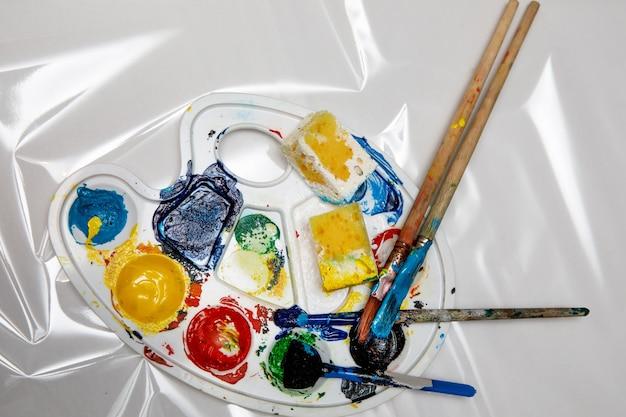 Colori ad acquerello e pennello sulla tavolozza d'arte.