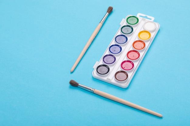 Pitture e spazzole dell'acquerello in scatola bianca, isolata