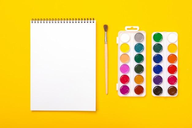 Pitture e spazzole dell'acquerello con l'album per la pittura sul fondo arancio