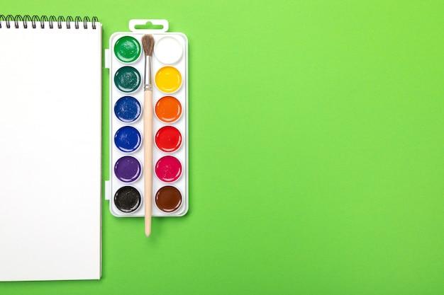 Pitture e spazzole dell'acquerello con tela per la pittura con copyspace su verde