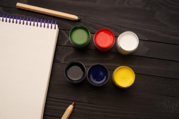 L'acquerello dipinge le matite degli strumenti di disegno del blocco note arte fondo di legno scuro
