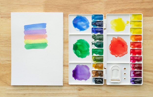 Colori ad acquerello impostati nella tavolozza bianca con carta bianca per lo sfondo. colorate acquerelli multicolori vernici in scatola di vernice.