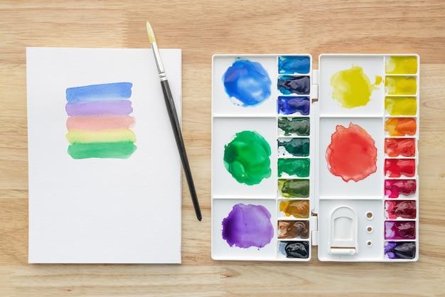 Set di colori ad acquerello con carta bianca. vernici aquarelle multicolori luminose per sfondo artistico.
