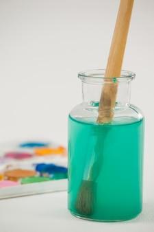 Tavolozza dell'acquerello e pennello con vernice blu immersa in acqua contro la superficie bianca