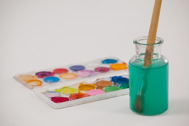 Tavolozza dell'acquerello e pennello con vernice blu immerso in un barattolo riempito d'acqua su sfondo bianco