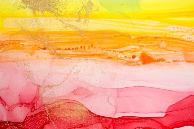 L'estratto giallo e rosso dell'acquerello macchia la struttura di pendenza dell'inchiostro del fondo