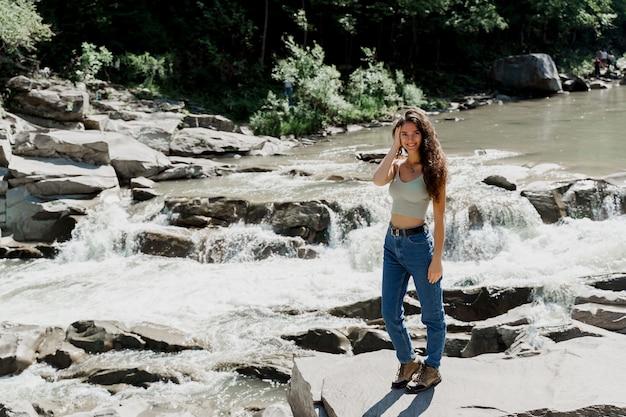Cascata nel fiume di montagna. ragazza in viaggio nelle montagne di karpathian e sensazione di libertà.