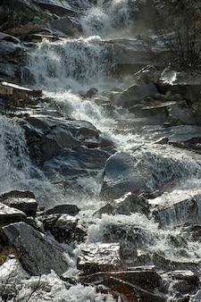 Cascata sul ruscello di montagna in montagna. acqua e pietre.