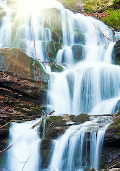 Cascate sul ruscello roccioso, che attraversa la foresta di montagna d'autunno e il sole