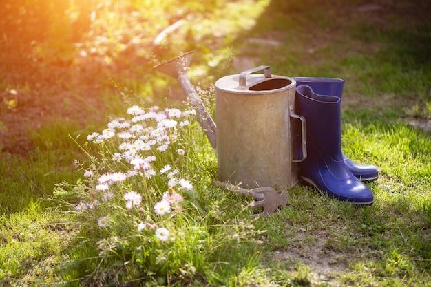 Annaffiatoio, stivali di gomma e ripper dopo il giardinaggio
