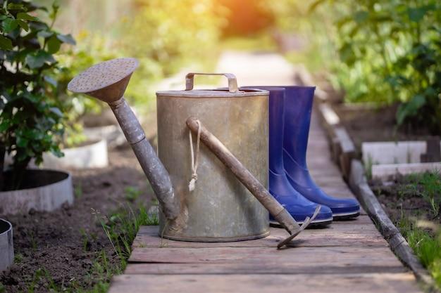 Annaffiatoio stivali di gomma e ripper dopo il giardinaggio