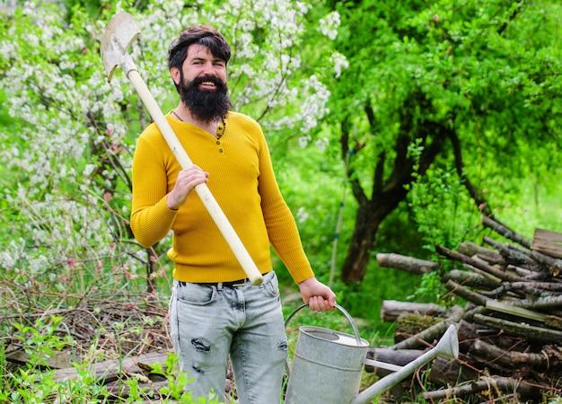 Irrigazione. giardinaggio. giardiniere sorridente con annaffiatoio e vanga. lavoro in giardino. azienda agricola. tempo di primavera