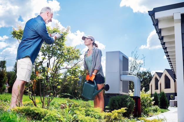 Albero d'innaffiatura. coppie amorose felici che indossano guanti e grembiuli che innaffiano insieme il loro piccolo albero nel giardino