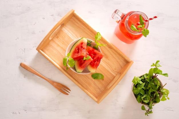 Bevanda all'anguria in vetro con fette di anguria su superficie bianca