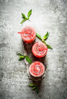 Succo di anguria in bottiglia con foglie di menta piperita. sul tavolo di pietra.