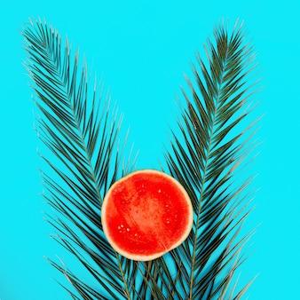 Anguria e palma su sfondo blu. arte vegana minimale piatta