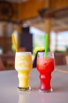 Frullato di anguria e ananas in un bicchiere con cannucce, bibita analcolica in una giornata estiva.